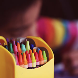 crayons with student in background