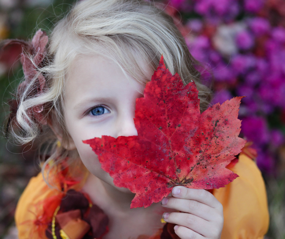 young girl with fall leaf